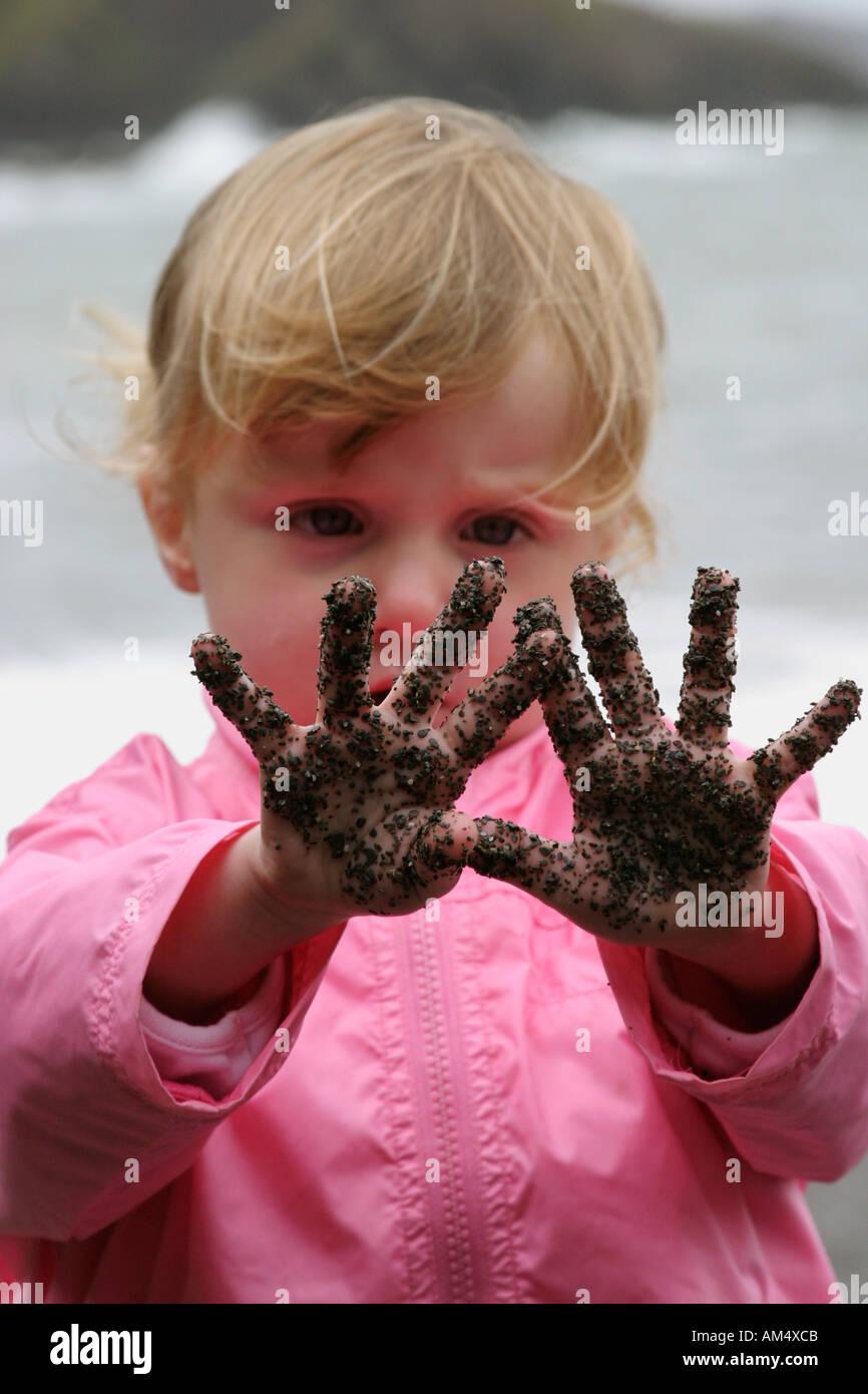 Une fille regarde dans l'émerveillement au sand sur ses mains Photo Stock