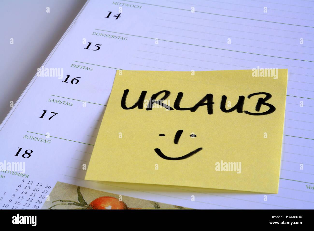 Note de rappel jaune Urlaub' (maison de vacances) sur la page d'un calendrier Photo Stock
