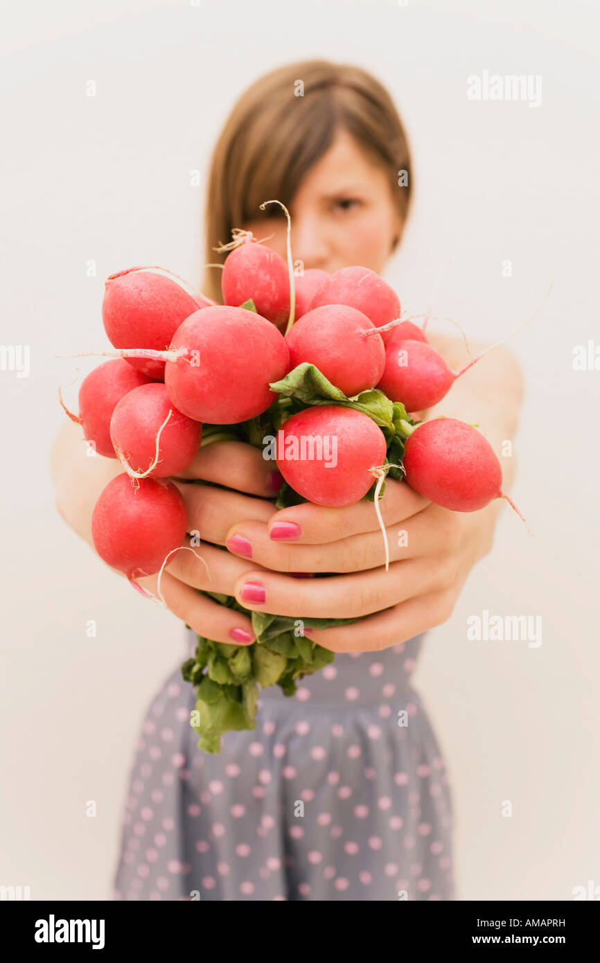 A woman holding a bunch of radishes Photo Stock