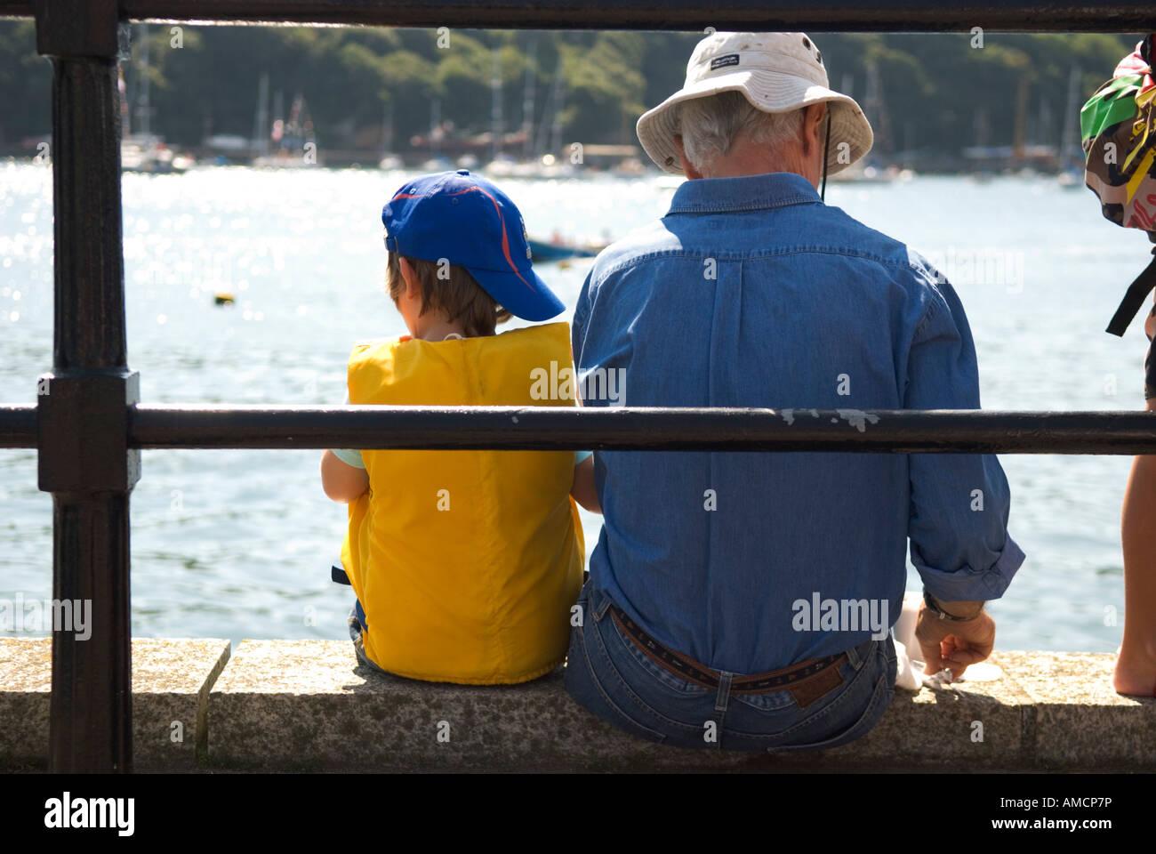 Une vue arrière de deux personnes assises sur le mur donnant sur la rivière fowey cornwall dans Banque D'Images