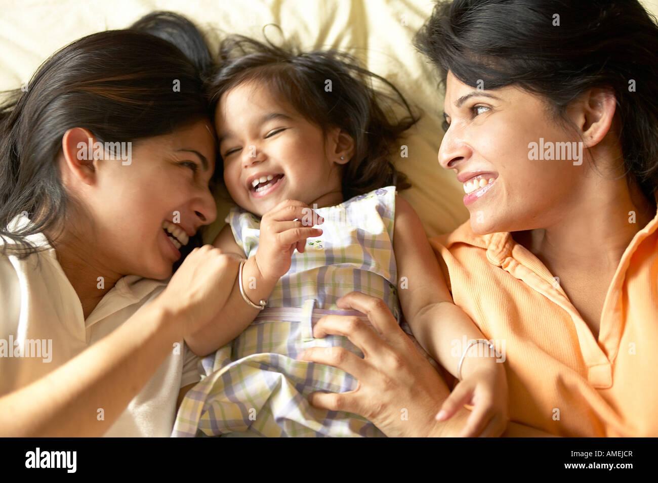 Deux femmes et le bébé sur le lit de pose Photo Stock
