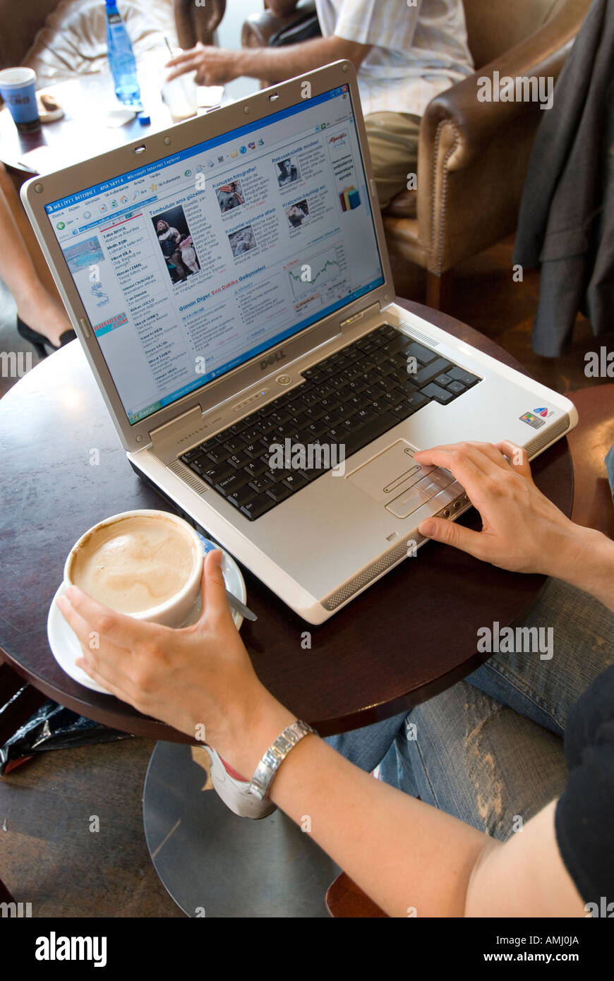 Jeune femme la navigation internet sur un ordinateur portable dans un café, England UK Photo Stock