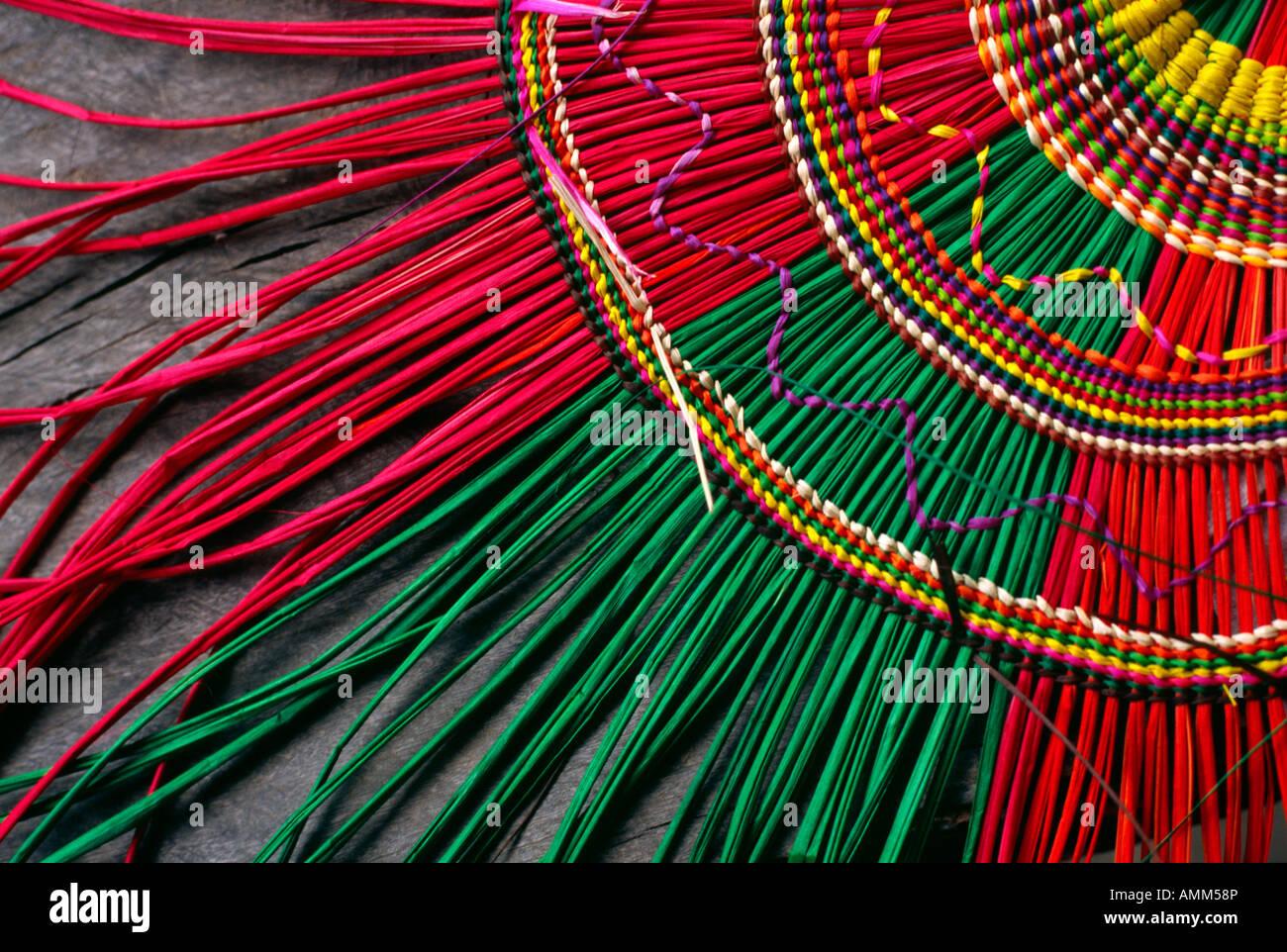 Roseaux sont colorés et tissés pour créer un réseau complexe de ventilateur dans un projet communautaire Photo Stock