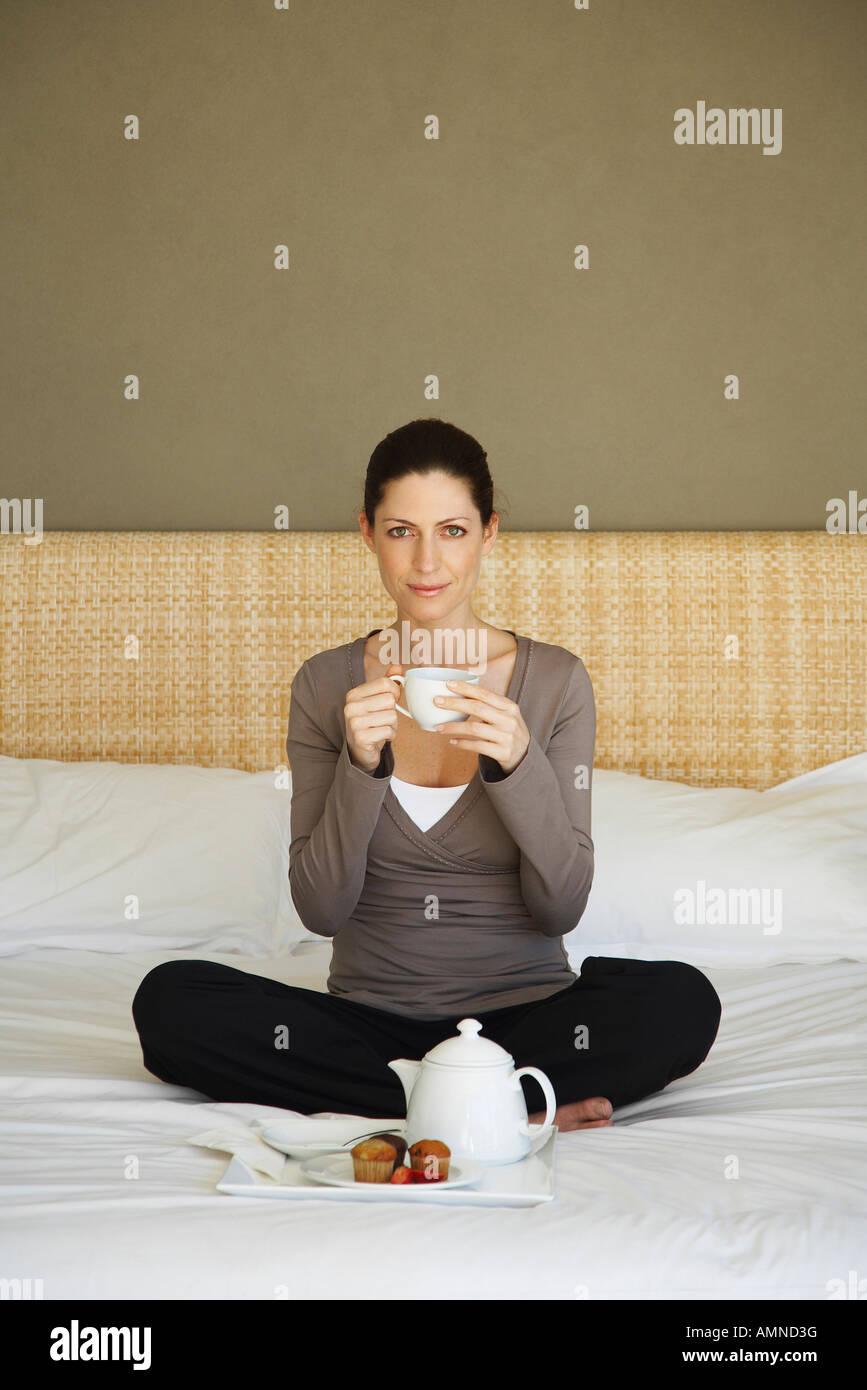 Femme prenant le thé on Bed Banque D'Images