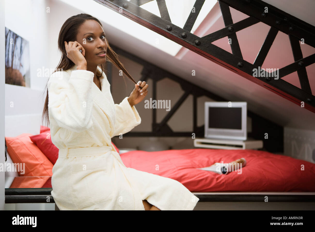 African woman in bathrobe talking on cell phone Banque D'Images