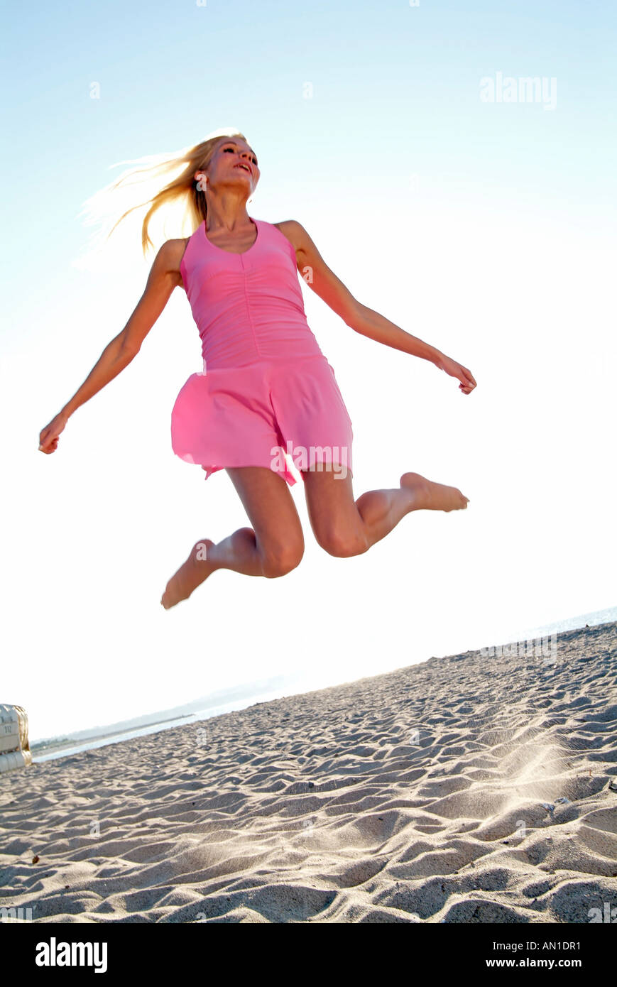 Young woman jumping at beachfront Photo Stock