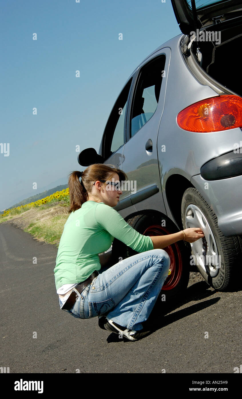 Femme changeant la roue / pneu pour un pneu de rechange sur sa voiture Photo Stock