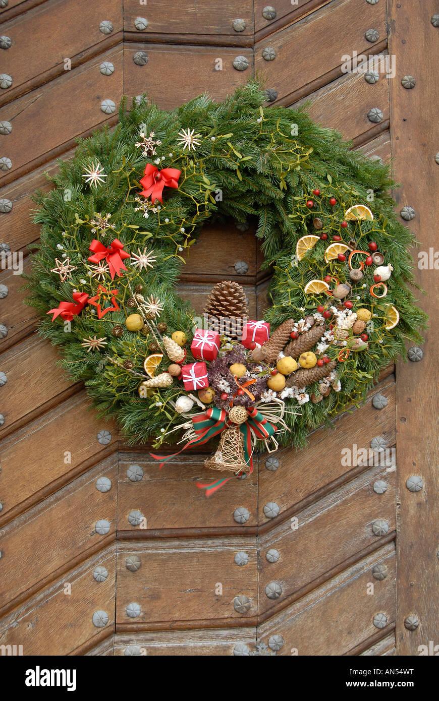Couronne De Porte Noel Design couronne de pin de noël accroché sur une porte en bois
