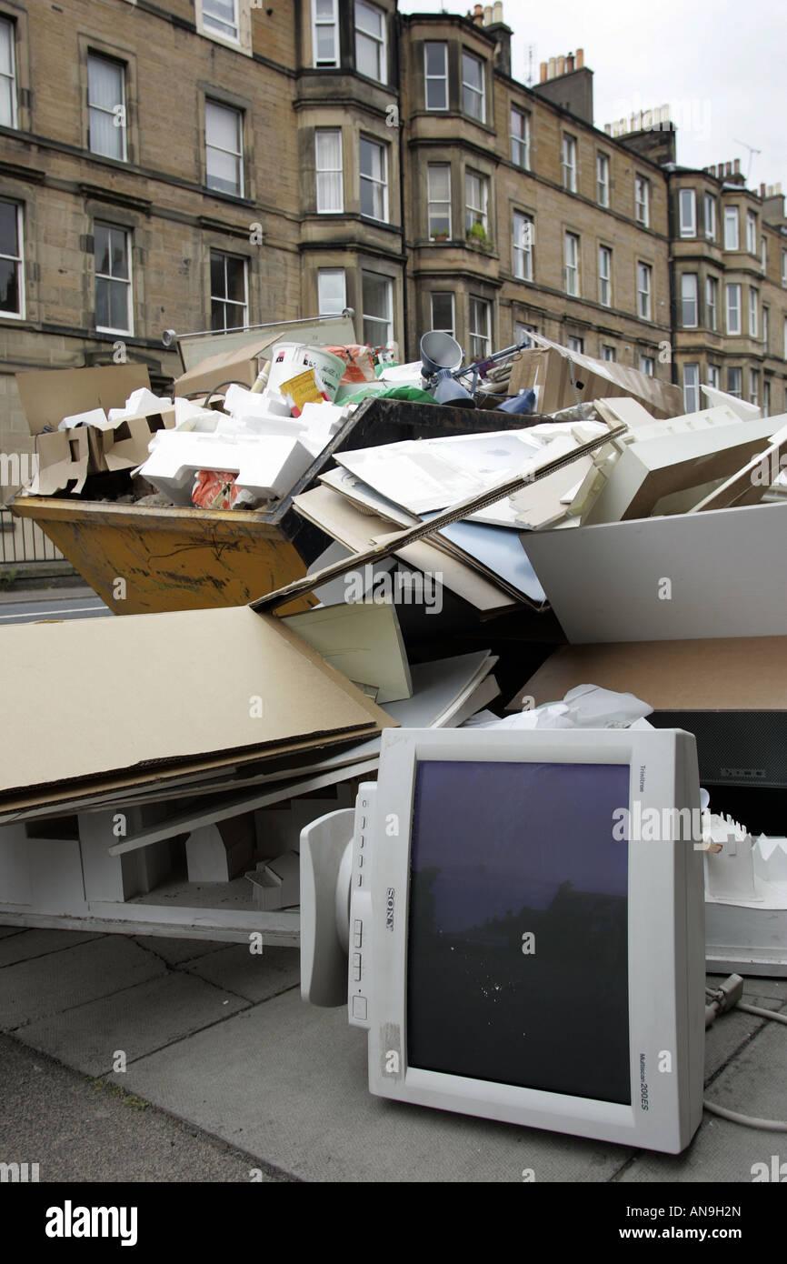 Plein d'un SKIP ET PLUS ruisselant de jeter le matériel de bureau. Photo Stock