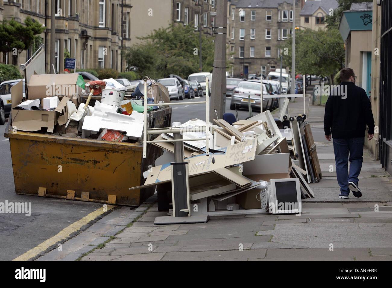 Un homme PASSE UNE SKIP TO FULL ET PLUS ruisselant de jeter le matériel de bureau. Photo Stock