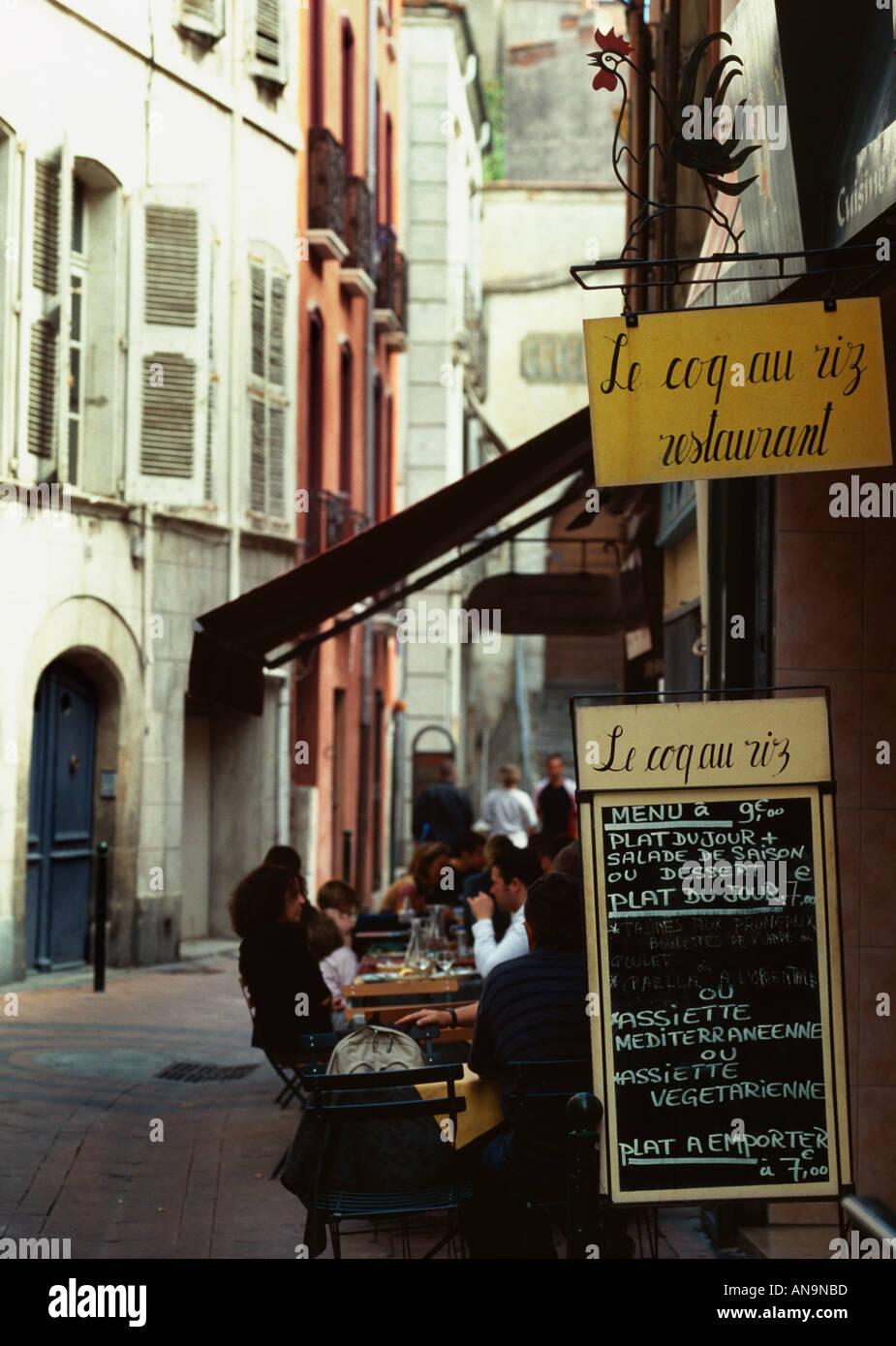 Vieille rue piétonne étroite typique avec café dans la vieille ville de Perpignan France Photo Stock