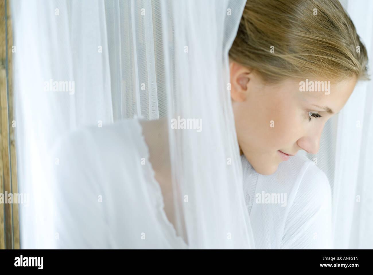Jeune femme regardant à travers les rideaux translucides, tête et épaules Photo Stock