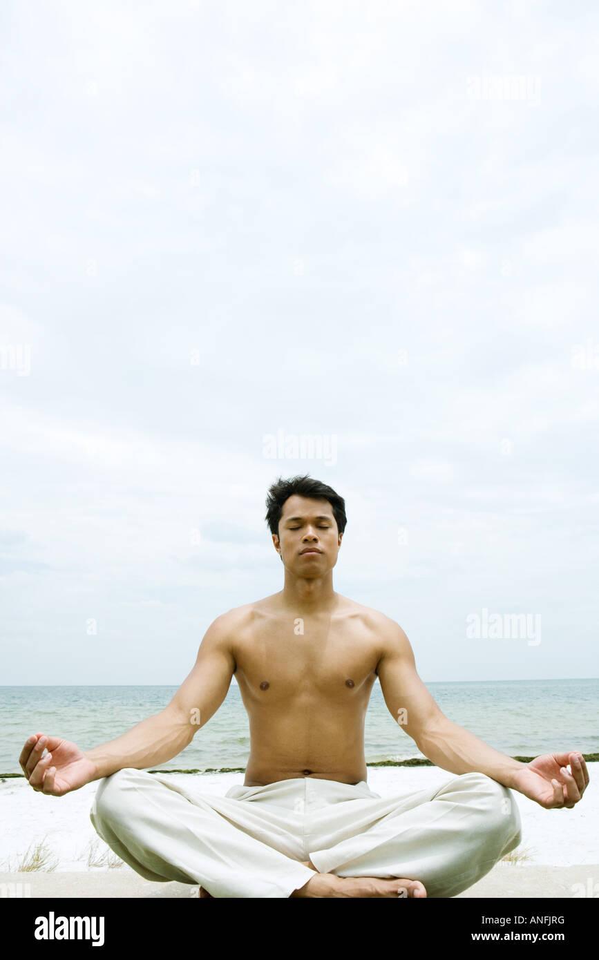 Nude man assis en position du lotus, de l'océan en arrière-plan Photo Stock