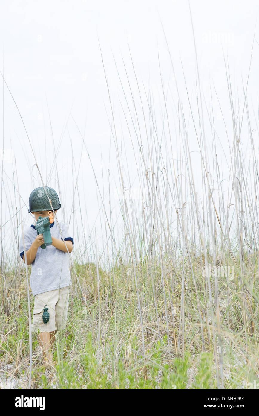 Jeune garçon faisant semblant d'être soldat, holding toy gun, looking at camera Banque D'Images