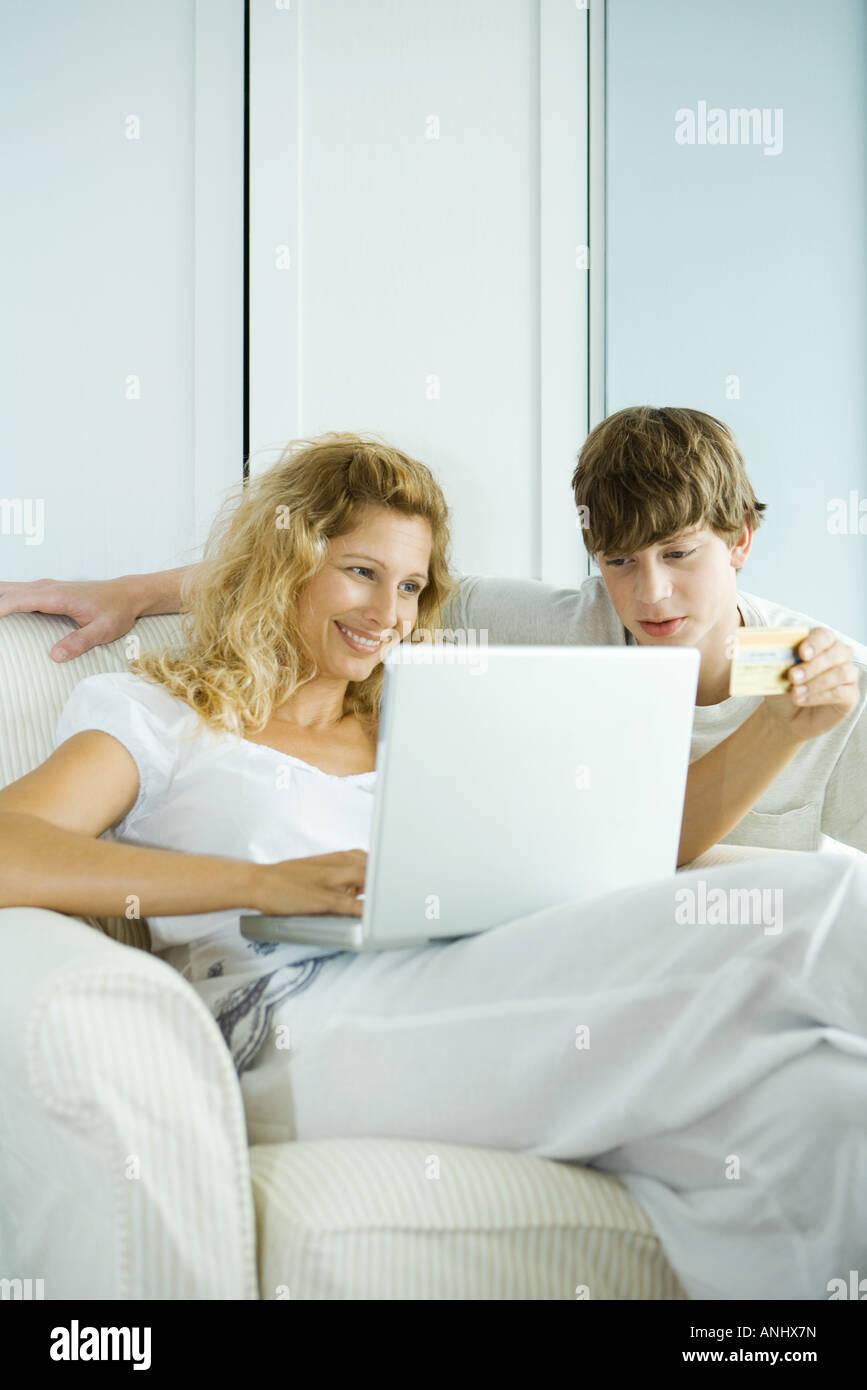 Femme et son adolescence, rendant achat en ligne par carte de crédit Photo Stock