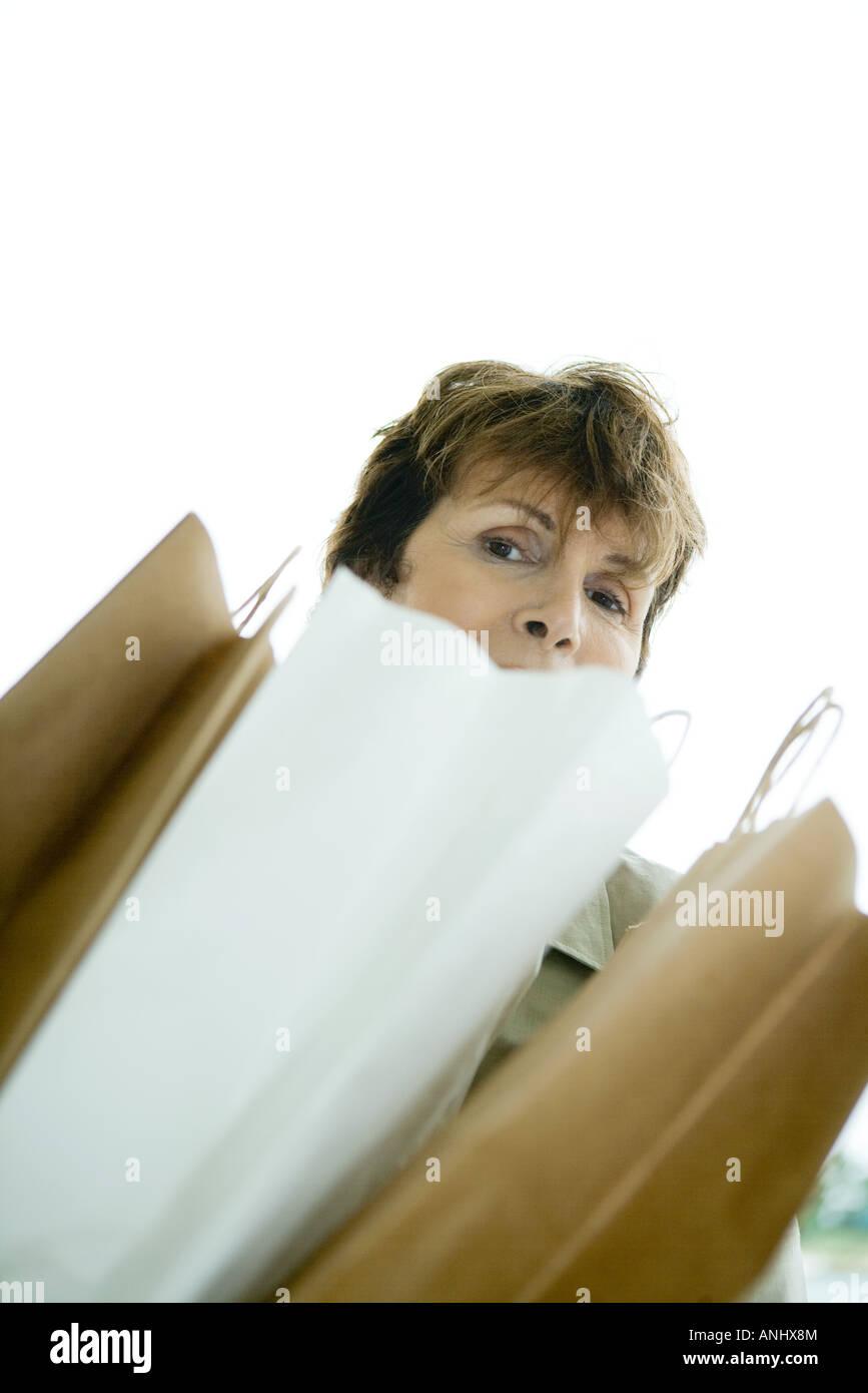 Femme à la recherche sur les sacs en papier Photo Stock