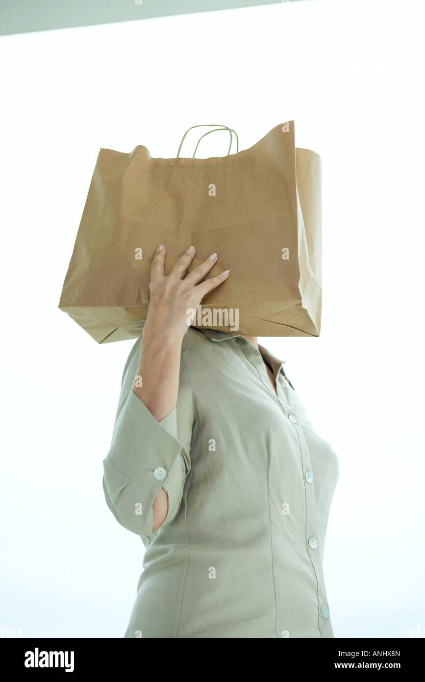 Woman holding paper bag sur épaule, tête cachée Photo Stock