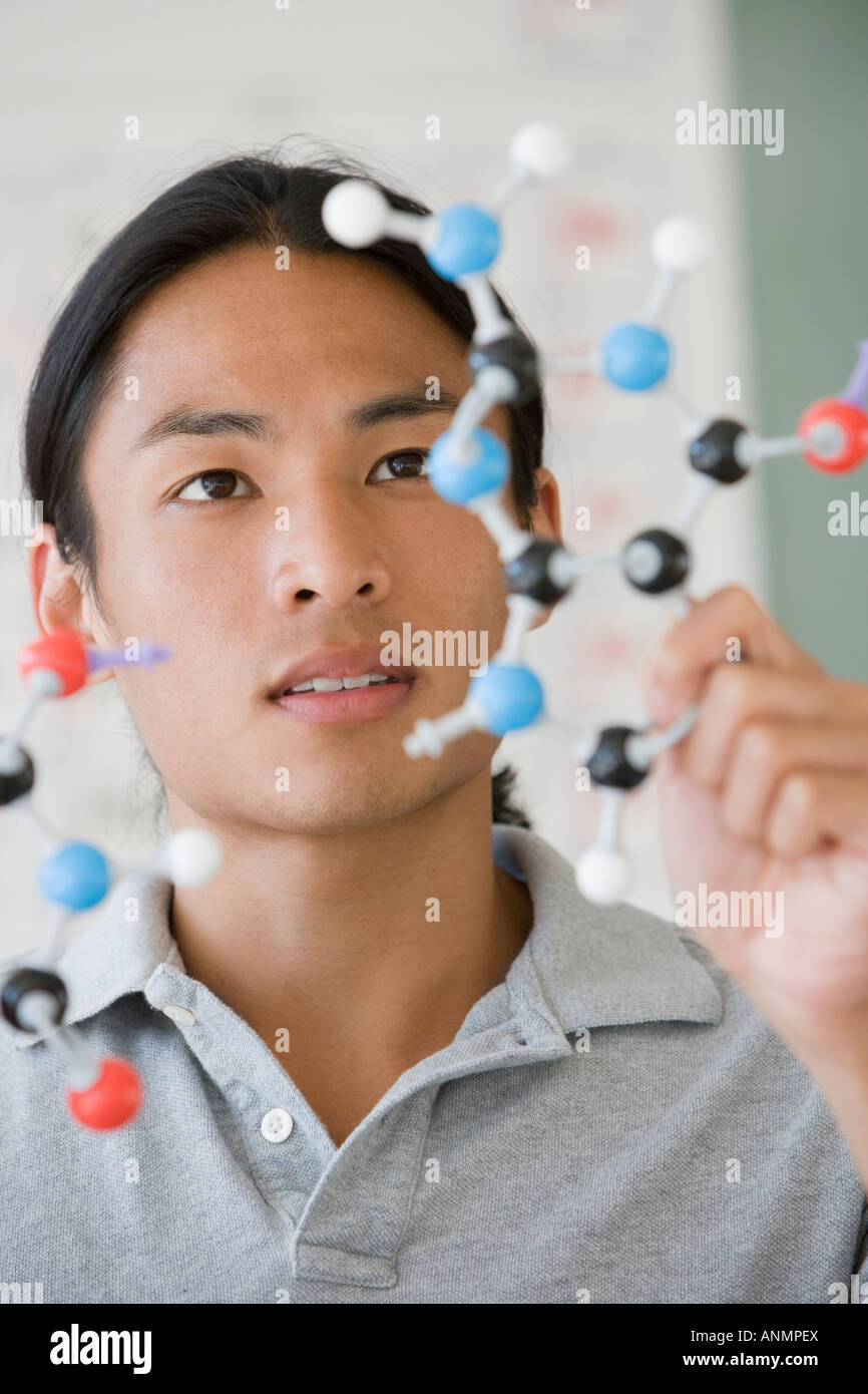 Asian male college student looking at molécule modèle Photo Stock