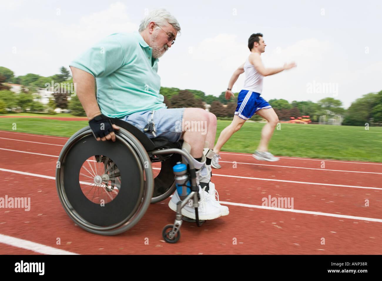 Jeune homme courir avec un homme handicapé sur un hippodrome. Photo Stock