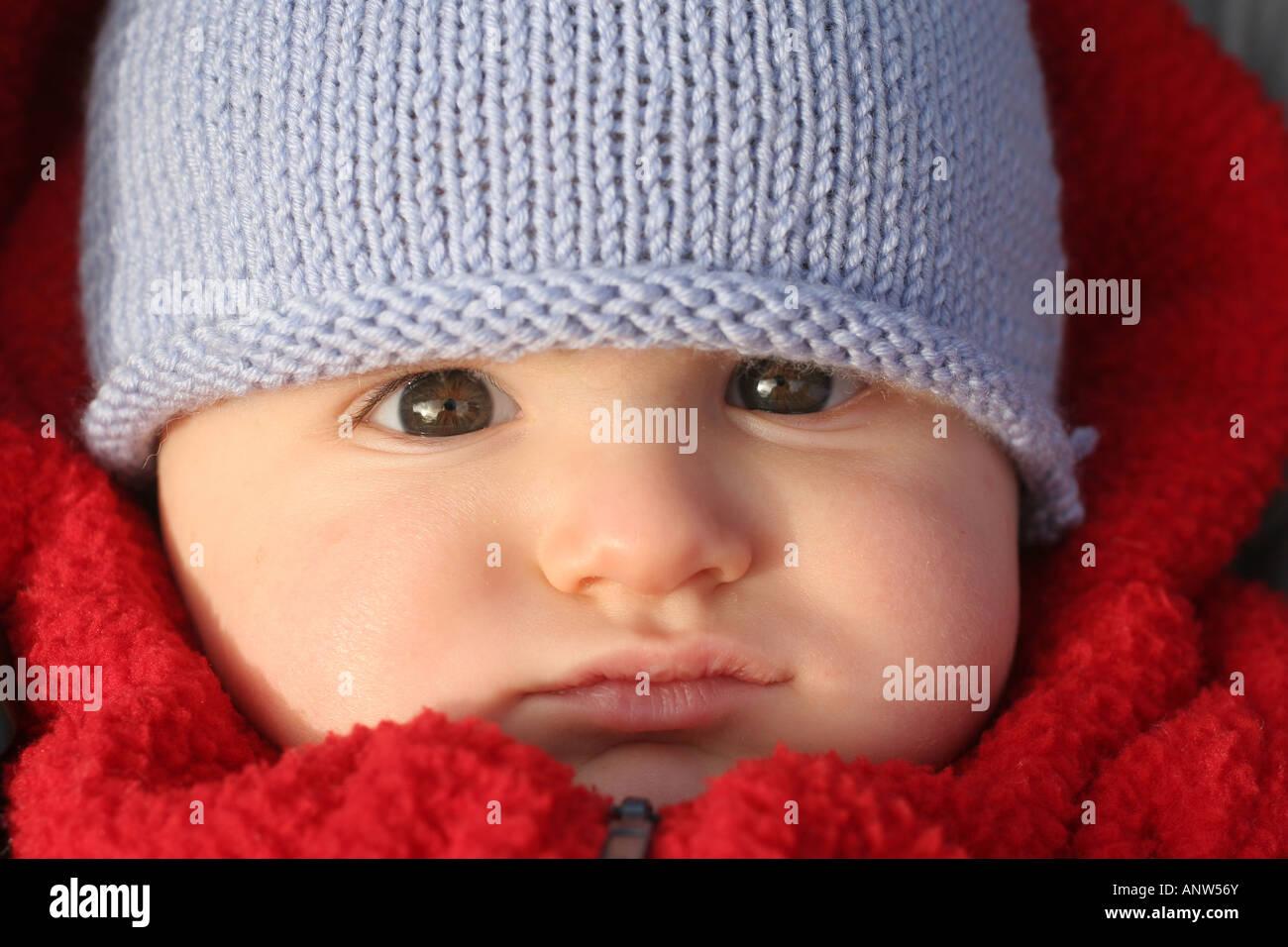 8 mois Bébé garçon avec manteau rouge et bonnet de laine bleu Photo Stock