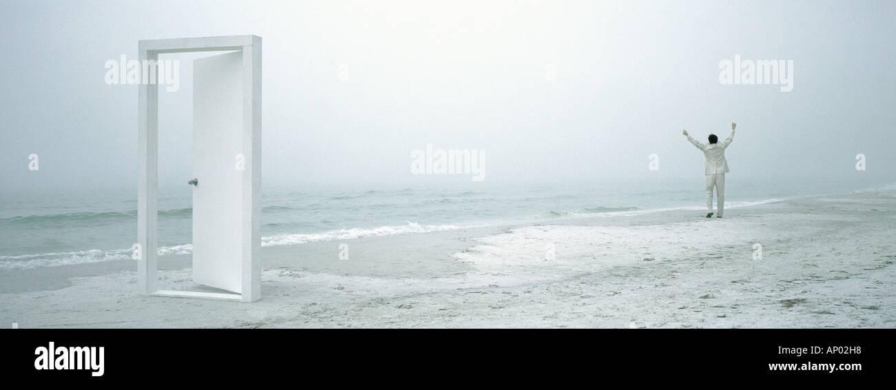 Man raising arms sur plage à distance, porte en premier plan Photo Stock