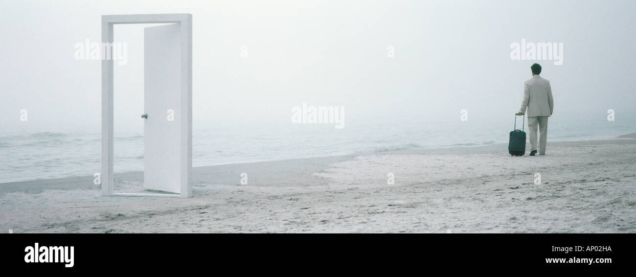 Man Walking with suitcase on beach à la mi-distance, porte en premier plan Photo Stock
