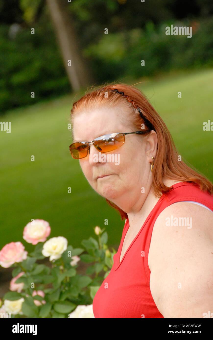 Femme avec des lunettes de soleil dans un jardin de roses Photo Stock d0a35216a78e