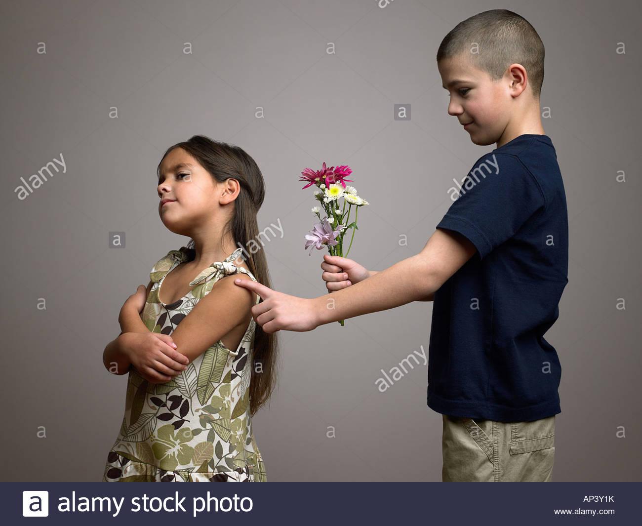 Garçon essayant de donner des fleurs à girl Photo Stock