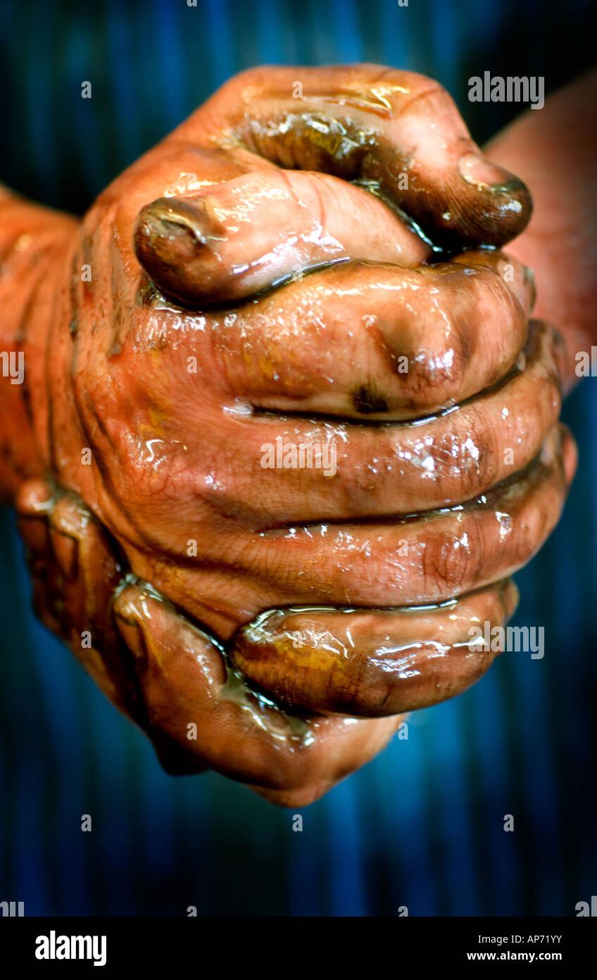 Les mains de l'Ouvrier couvert d'huile, les doigts jointes, en garage de réparation automobile shop. Photo Stock