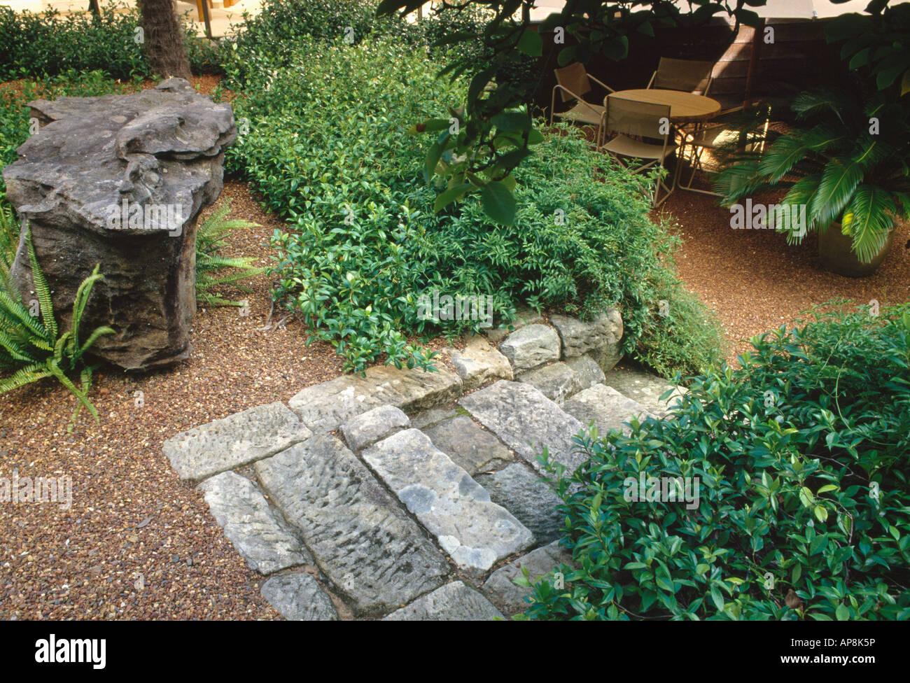 Gros rocher à côté d\'arbustes verts et marches de pierre ...