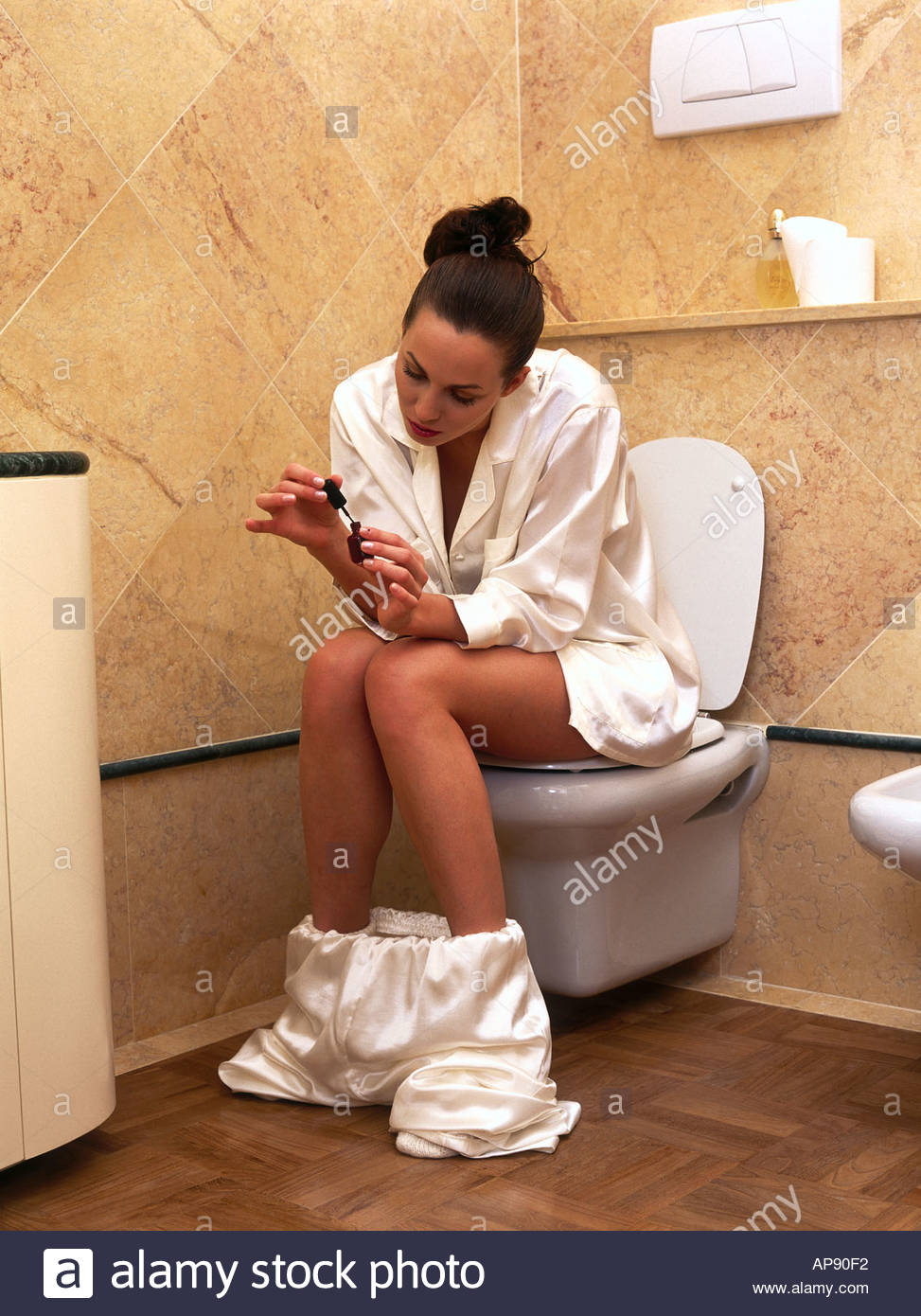Femme assise sur des ongles vernis et wc