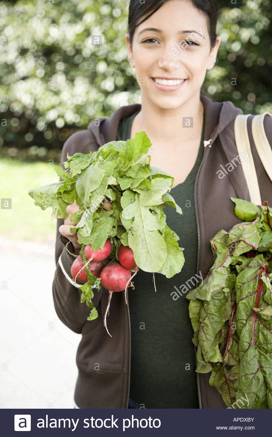 Hispanic woman holding bunch of radishes Photo Stock