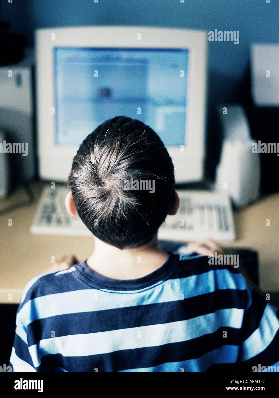 Vue arrière d'un enfant à l'aide d'un ordinateur Photo Stock