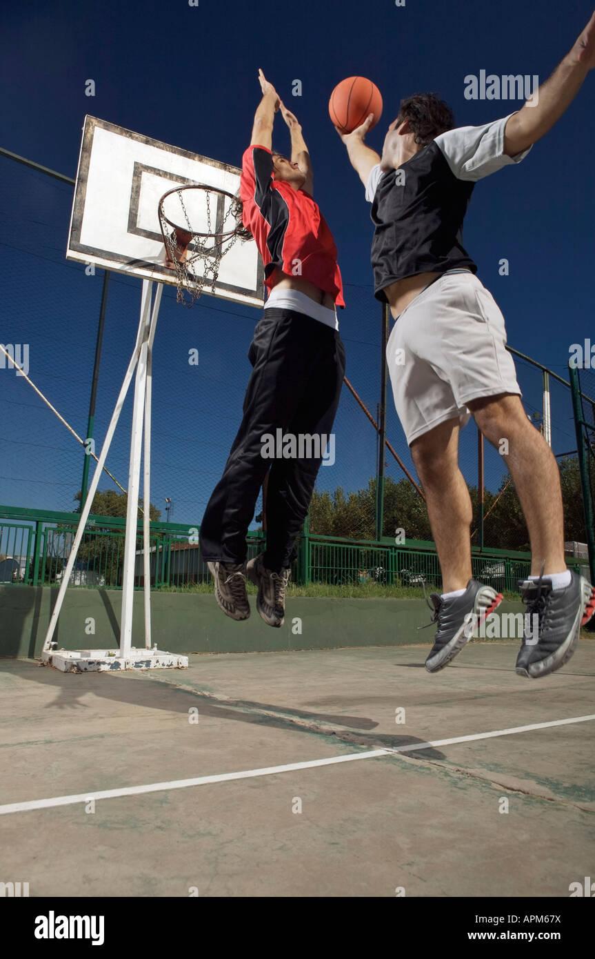 Deux jeunes hommes jouant au basket-ball Photo Stock