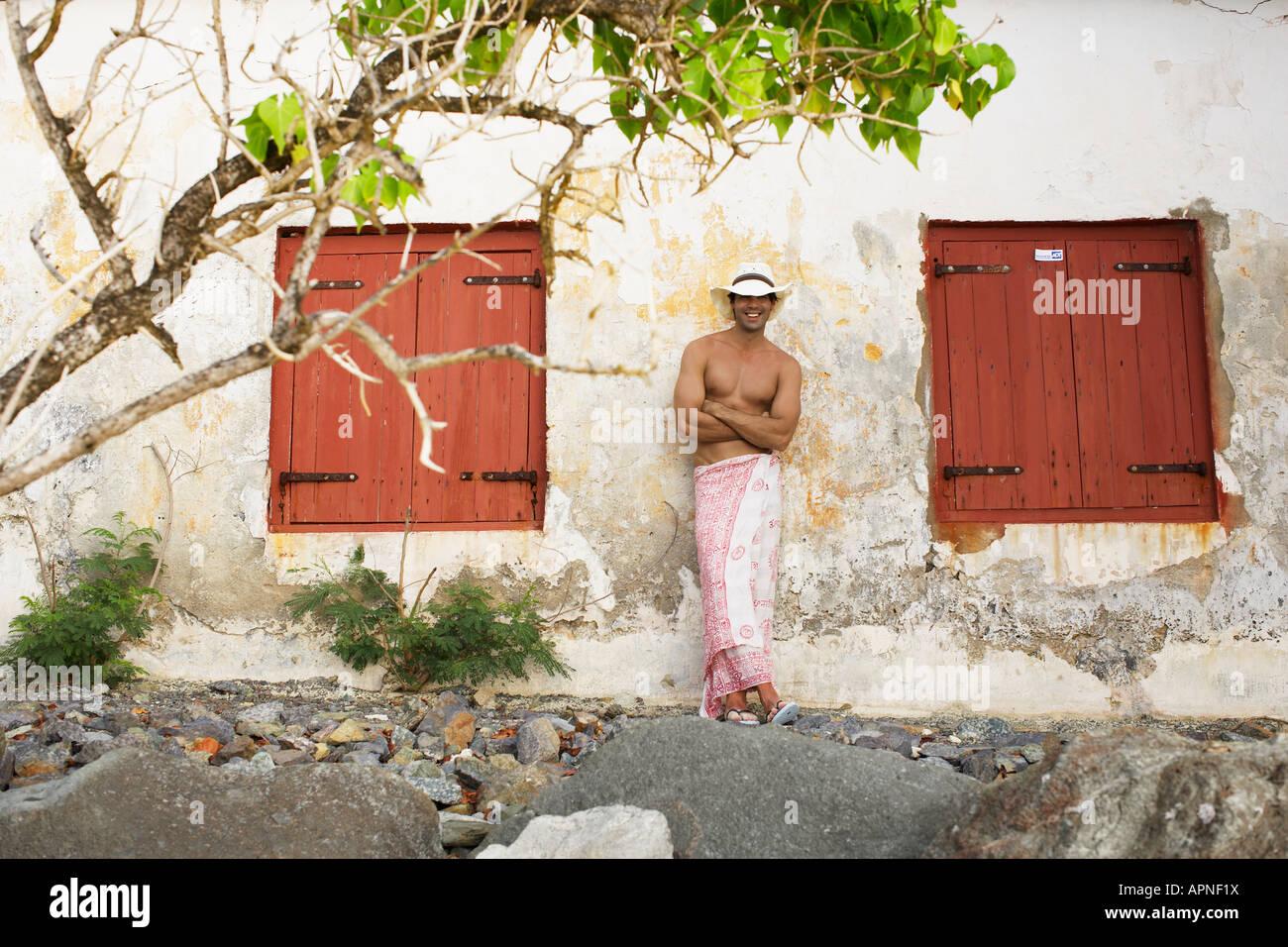Jeune homme en sarong et hat standing by old house Banque D'Images