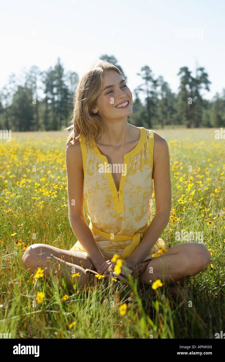 Jeune femme assise dans un champ de fleurs sauvages Banque D'Images