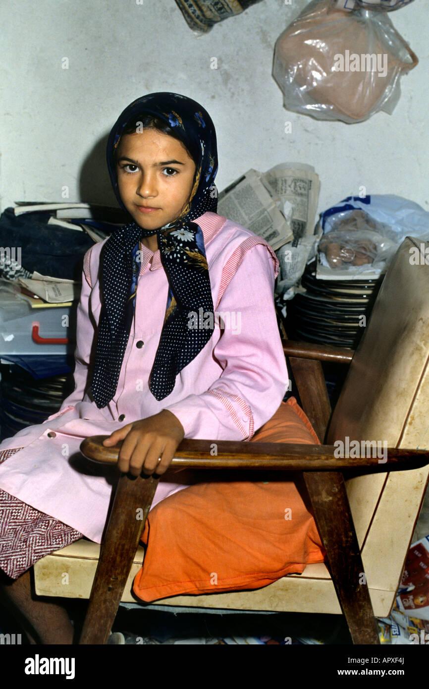520e4f1be192 Jeune fille tunisienne assis sur une chaise portant un foulard et une tunique  rose