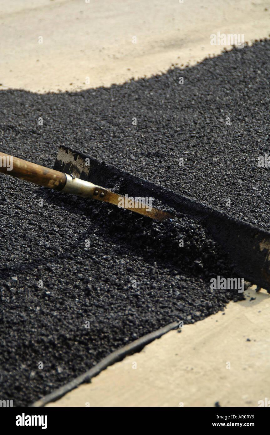 Un travailleur est frais lissage tar Banque D'Images