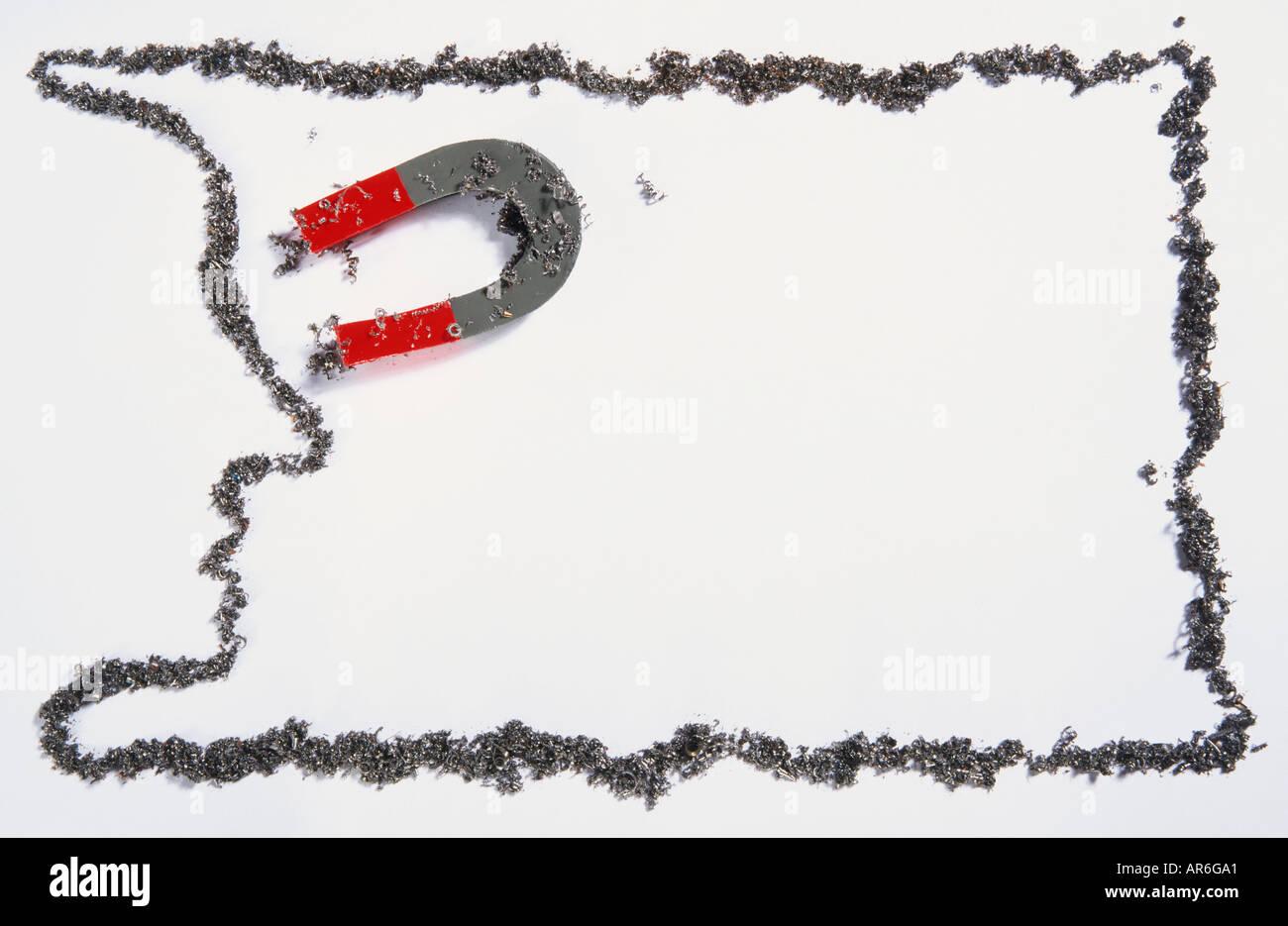 Gris en forme de fer et l'aimant rouge entouré d'une ligne de limaille de fer rectangulaire Photo Stock