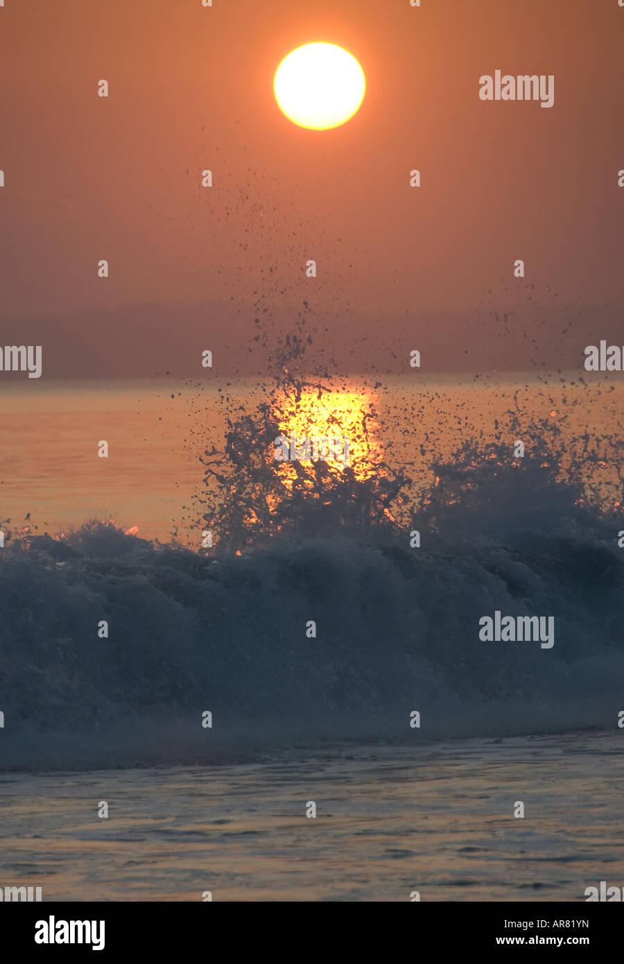 Le coucher et le déferlement des vagues Photo Stock