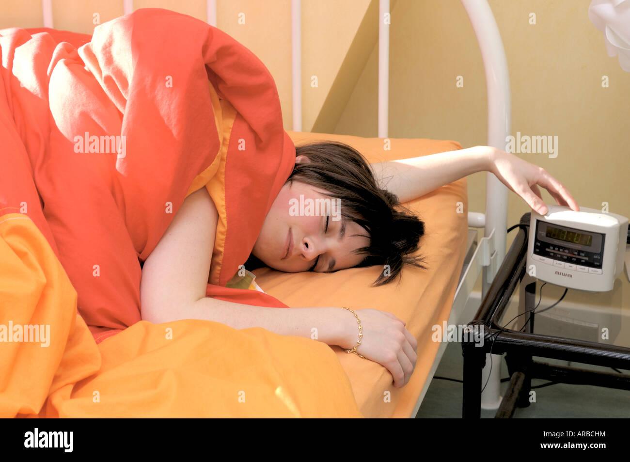Sleepy / adolescent paresseux éteindre son réveil Photo Stock
