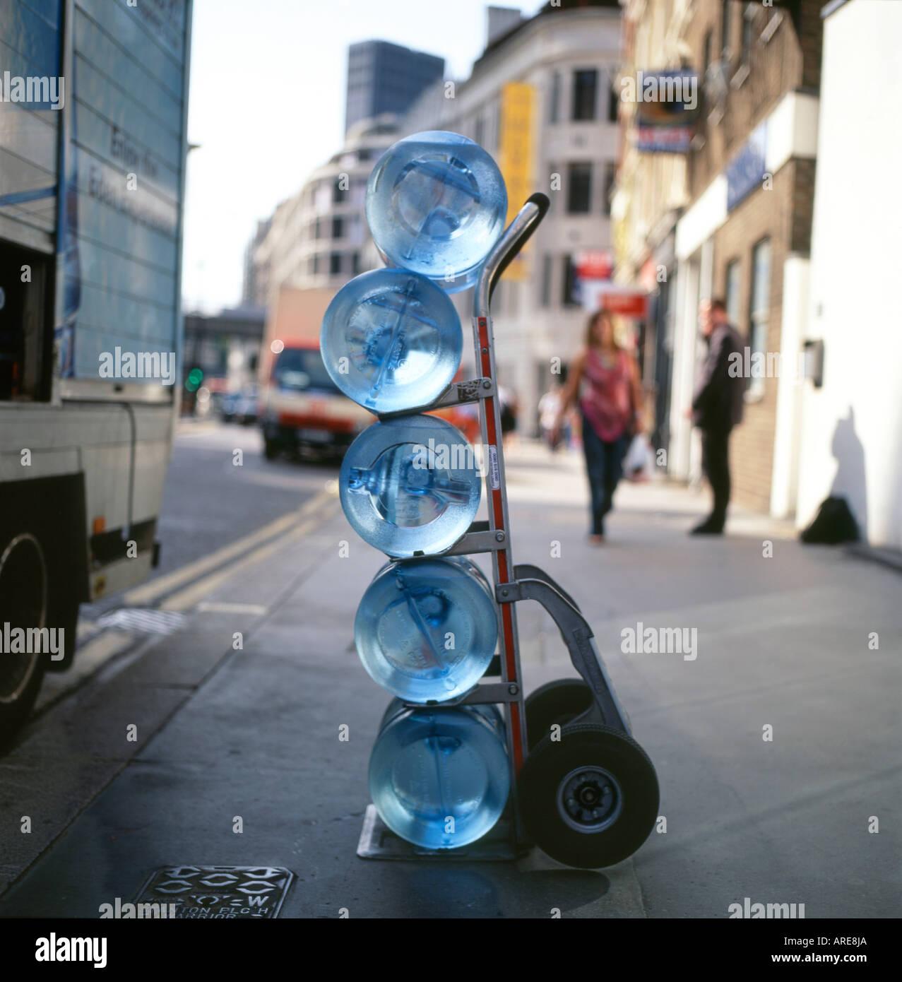 Refroidisseur d'eau bouteilles empilées sur un chariot de livraison dans une rue du centre de Londres, Angleterre, Royaume-Uni Photo Stock