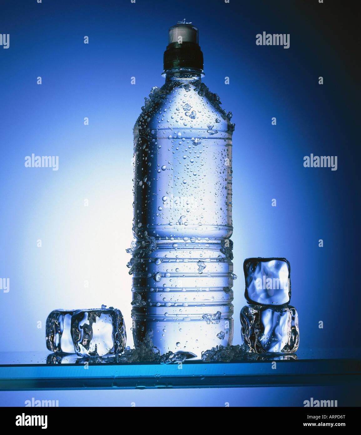 Bouteille d'eau avec des cubes de glace Photo Stock