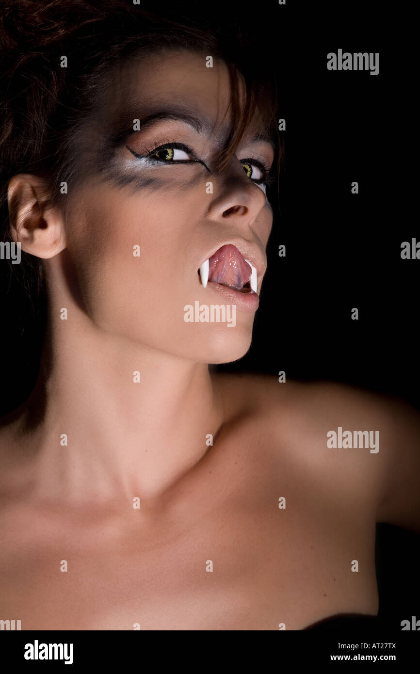 Femme avec des dents de vampire léchant ses lèvres sur fond noir Photo Stock