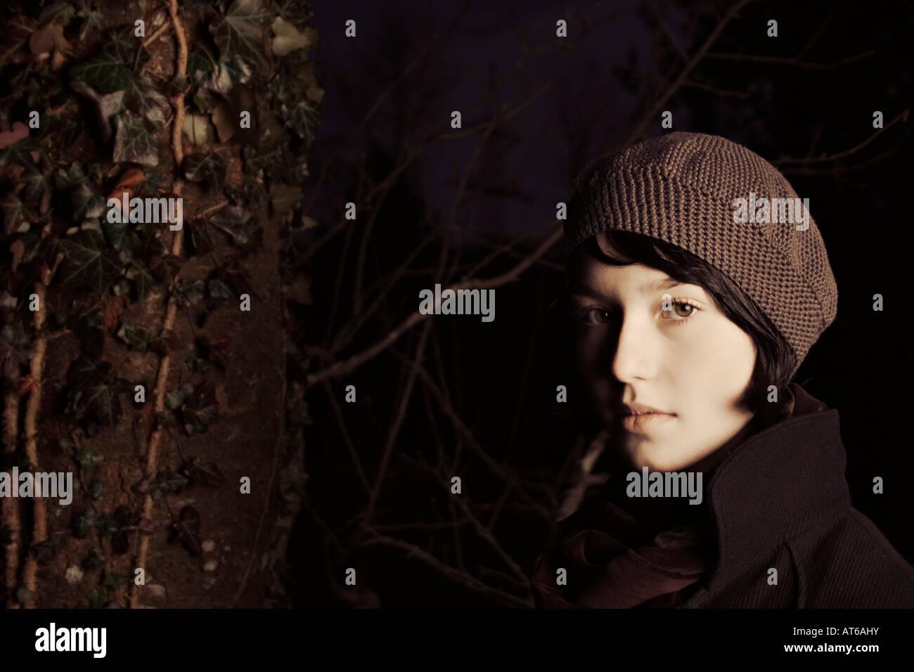 Jeune femme debout près d'un arbre Photo Stock