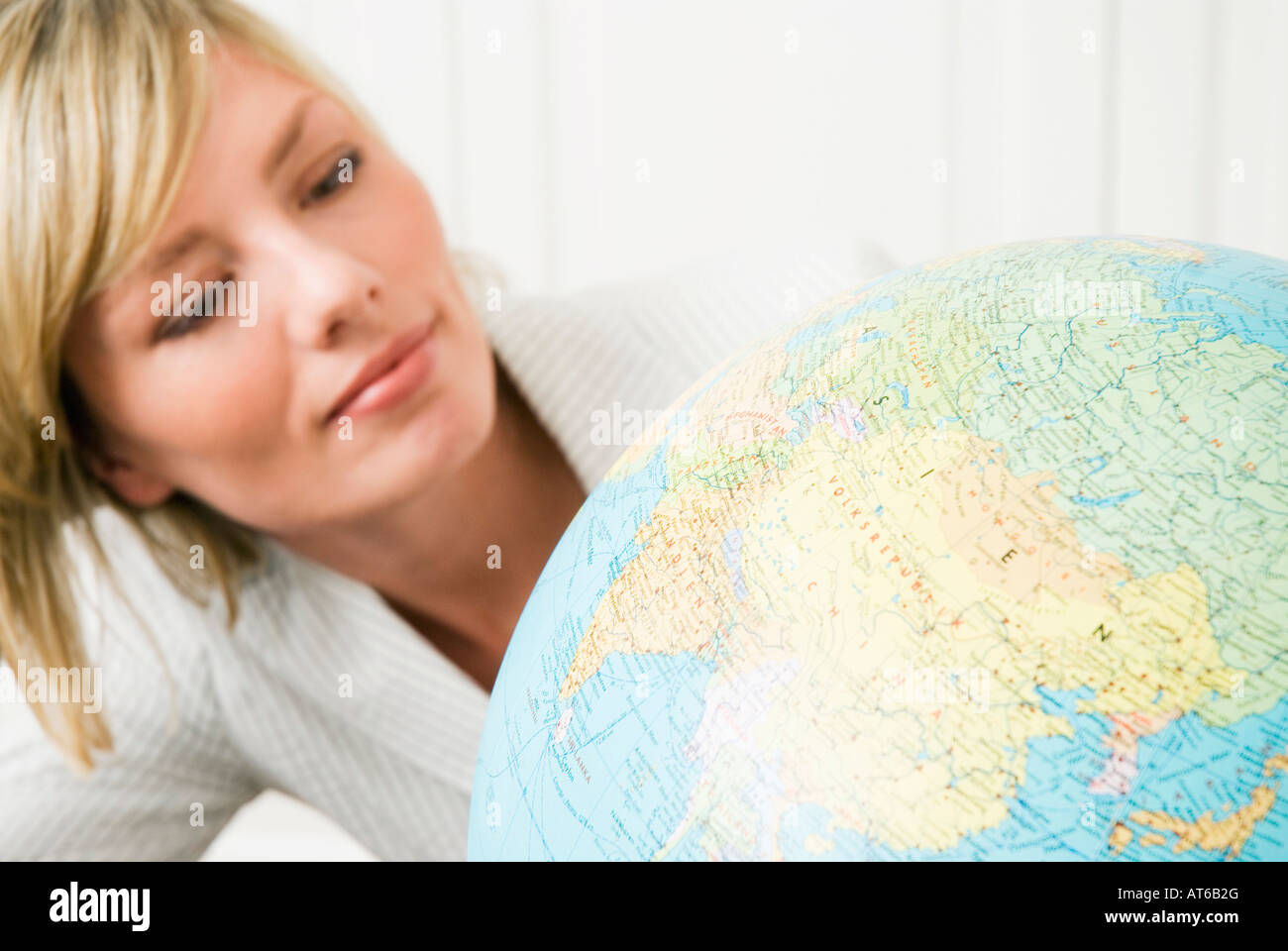 Young businesswoman looking at globe, portrait, close-up Photo Stock