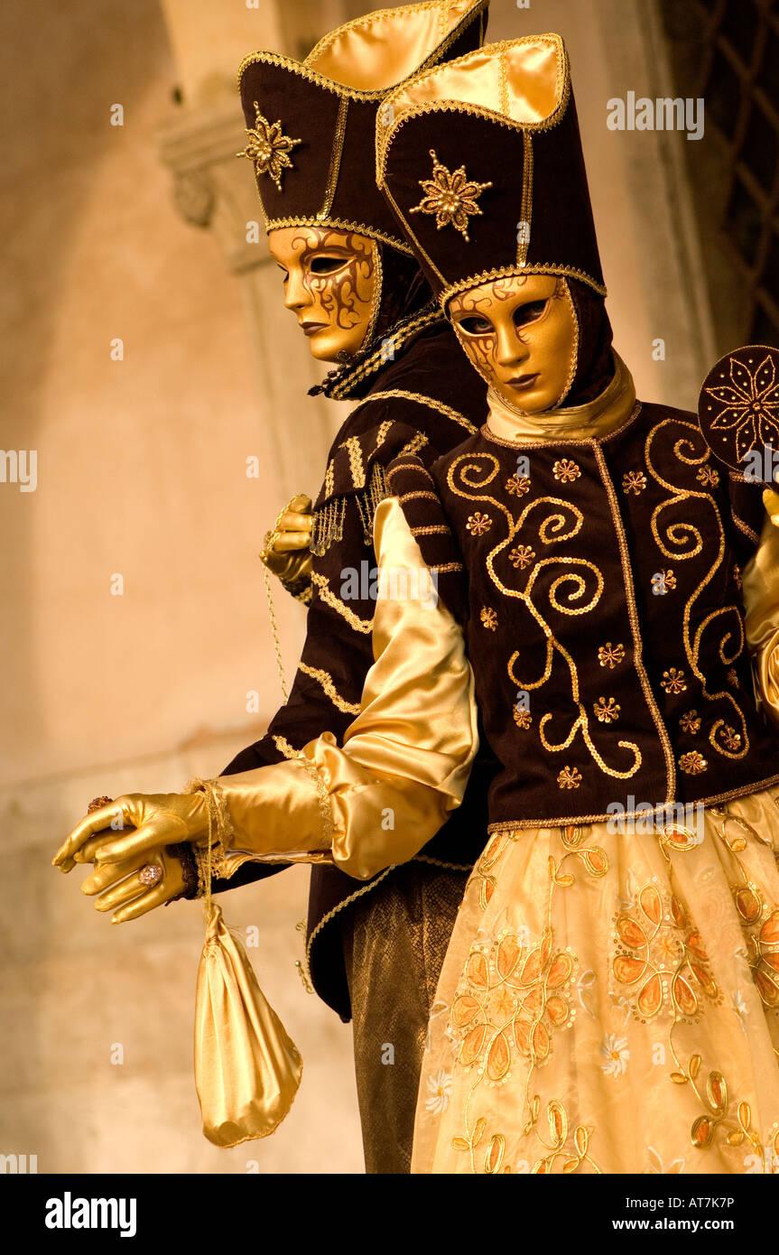 Masque de CARNAVAL DE VENISE FESTIVAL MAN & WOMAN EN OR DES MASQUES, des costumes d'or et marron Banque D'Images