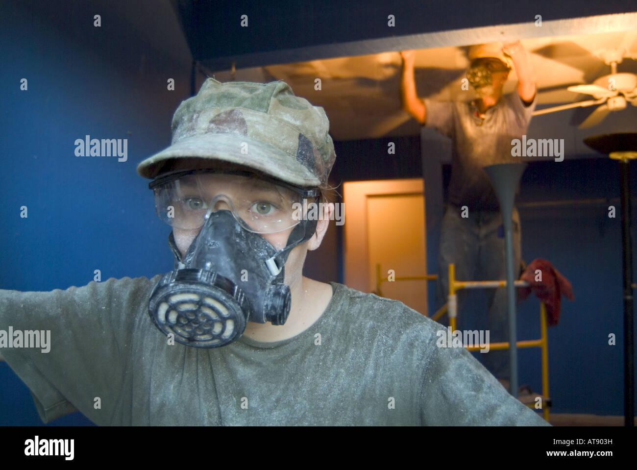 Accueil Travaux de construction. Le port d'un masque de ventalation adolescent tout en aidant à gratter le plafond avec plus african american man Banque D'Images