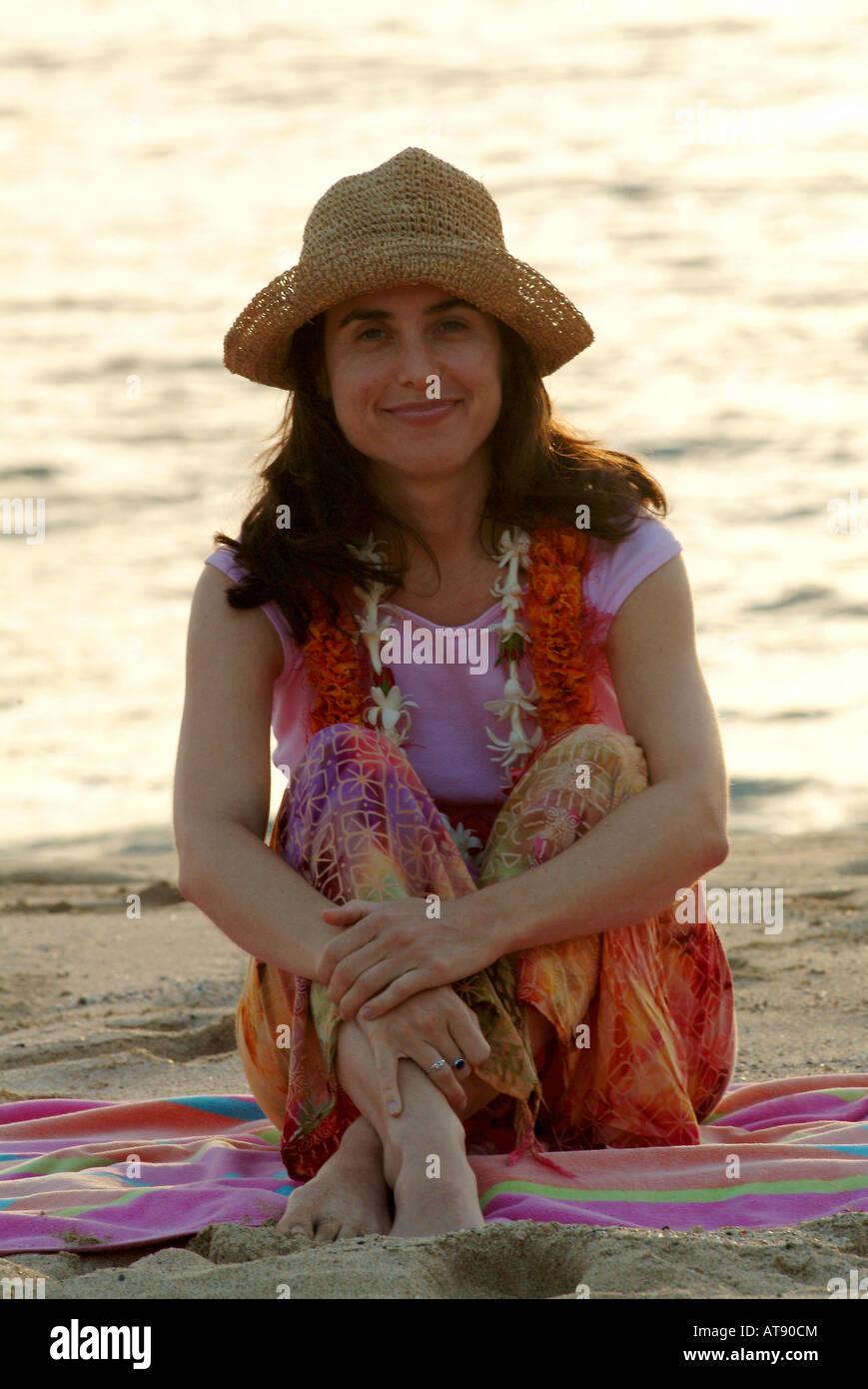 Femme juive au milieu de trente est assise sur serviette à la plage portant un chapeau et une fleur leis Banque D'Images