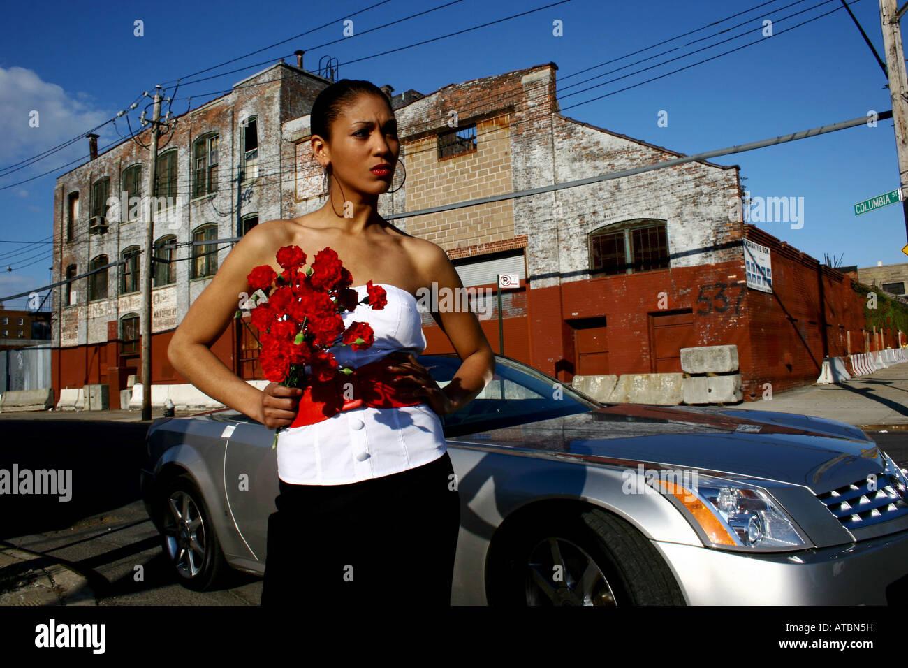 Jeune Femme sophistiquée HOLDING FLOWERS. Voiture Cadillac convertible en arrière-plan. Photo Stock